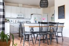 a chic farmhouse space with white walls and laminate-looking vinyl, with white cabinets, a dining table and black chairs