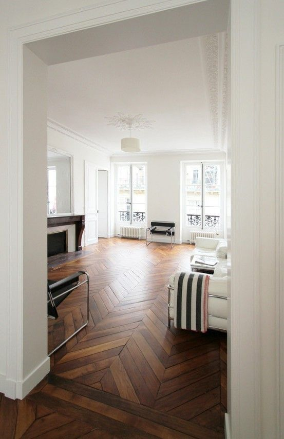 a chic living room with white walls and a rich stained parquet floor, white and black furniture and a refined fireplace