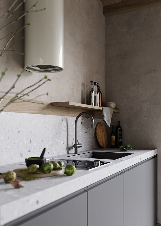 a chic minimalist grey kitchen with a grey terrazzo countertop and a backsplash, a small hood and a floating shelf is elegant