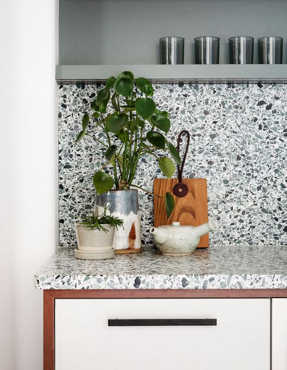 a chic modern kitchen in white with a catchy and bold terrazzo backsplash and countertops and a floating shelf that matches