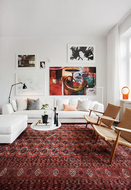 a chic modern living room with a white sofa and an ottoman, rattan chairs, a bright printed rug and a gallery wall