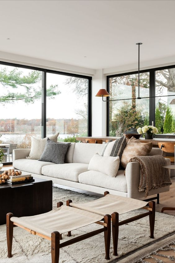 a chic modern living room with a white sofa, printed pillows, wooden stools, a dark coffee table and a pendant lamp