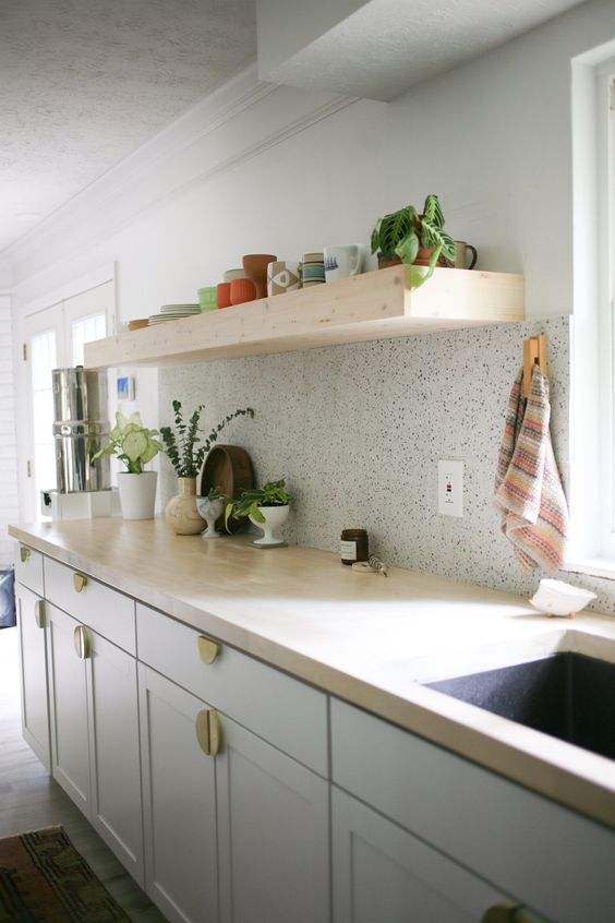 a chic neutral kitchen with butcherblock countertops and a neutral terrazzo backsplash plus a thick wooden shelf over it