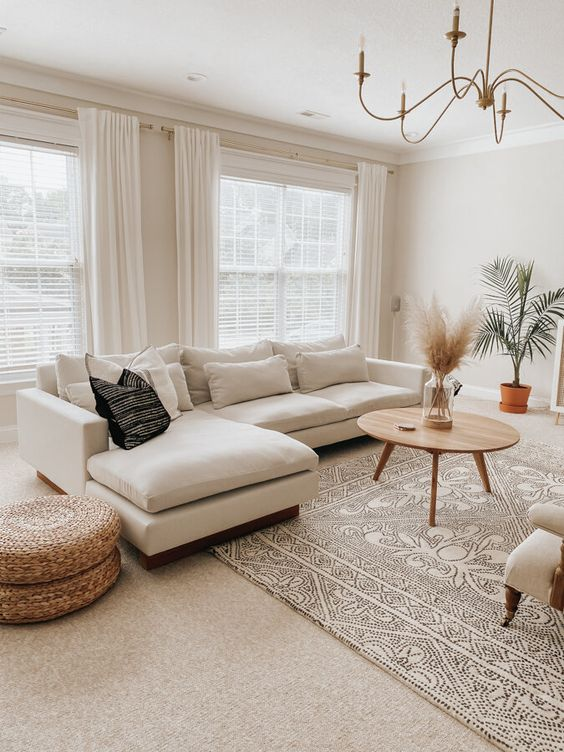 a chic neutral living room with a white sectional, a matching refined chair, rattan poufs, a round wooden table and a potted plant
