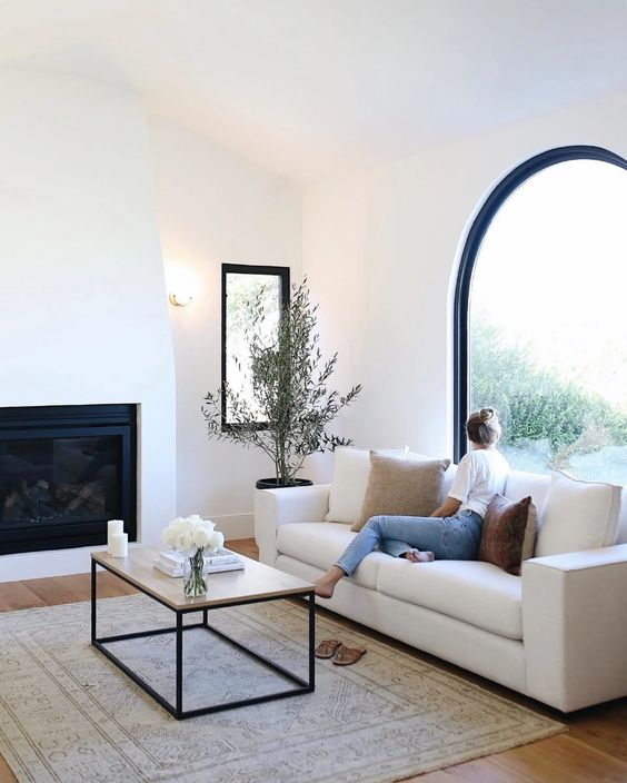 a chic neutral living room with an arched window, a built-in fireplace, a white sofa and a coffee table and a potted mini tree