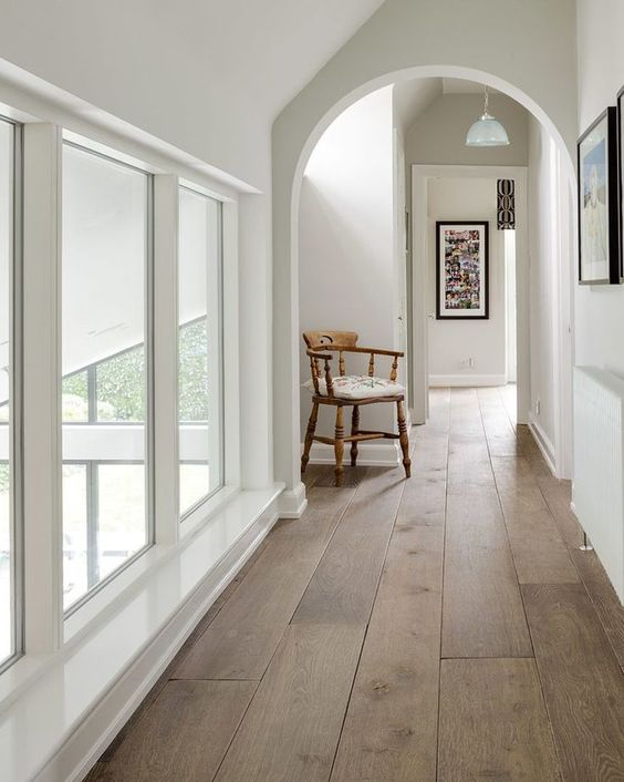 a chic space with an arched doorway, laminate floors and a vintage chair plus much natural light coming through windows