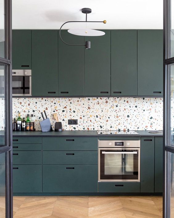 a chic teal kitchen with black countertops and a bright terrazzo backsplash plus a bold chandelier is a very stylish space