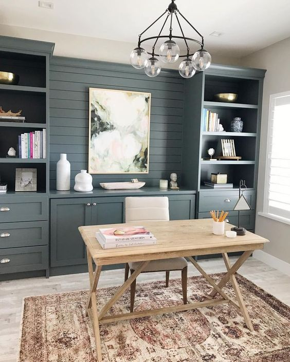 a classic coastal home office with a large slate grey built-in storage unit, a wooden trestle desk and an upholstered chair, a chandelier