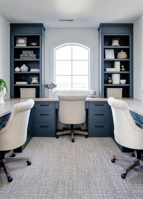 a classic coastal home office with a navy built-in storage and desk unit that takes the whole room and creamy upholstered chairs