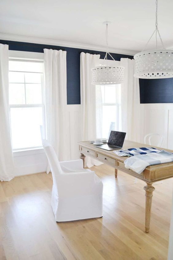 a classic nautical home office with navy walls and white paneling, a wooden desk, a white chair, white curtains and pendant lamps
