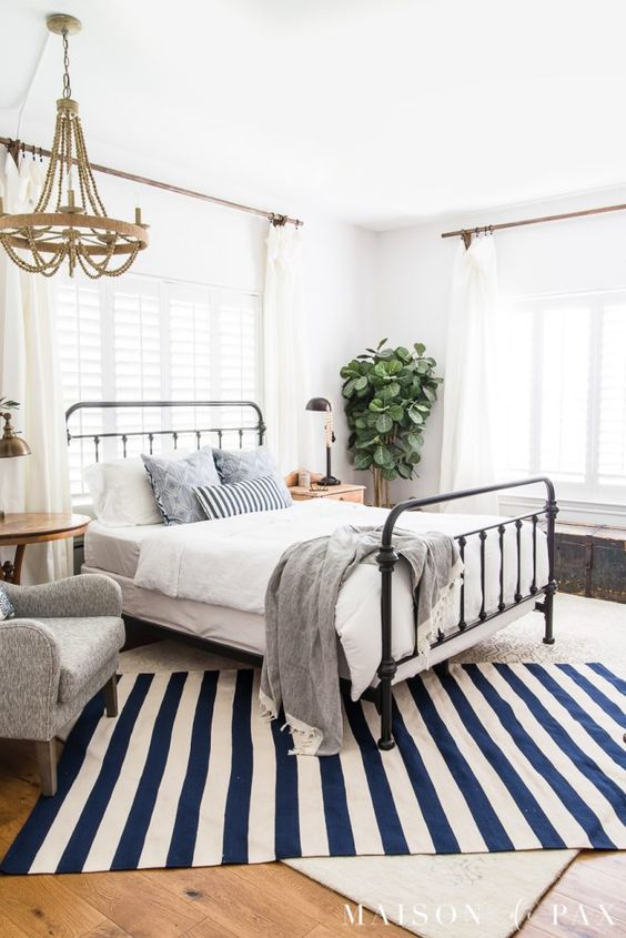 a classic summer bedroom with a metal bed, an upholstered chair, layered rugs, a wooden chandelier and a potted plant