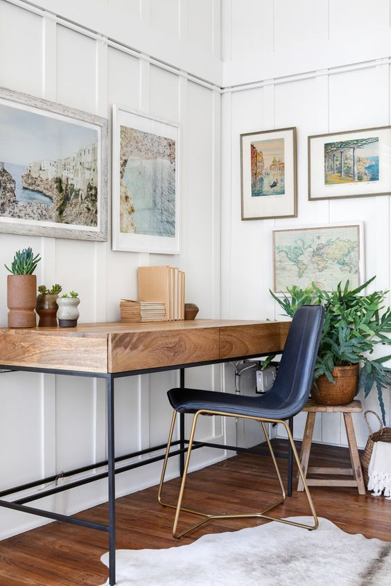 a coastal home office nook with white panels on the walls, a wooden desk, a navy chair and lovely beach artworks