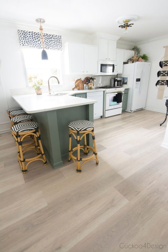 a coastal kitchen with white walls and a vinyl floor, white and green cabinetry, rattan stools and a printed curtain is chic