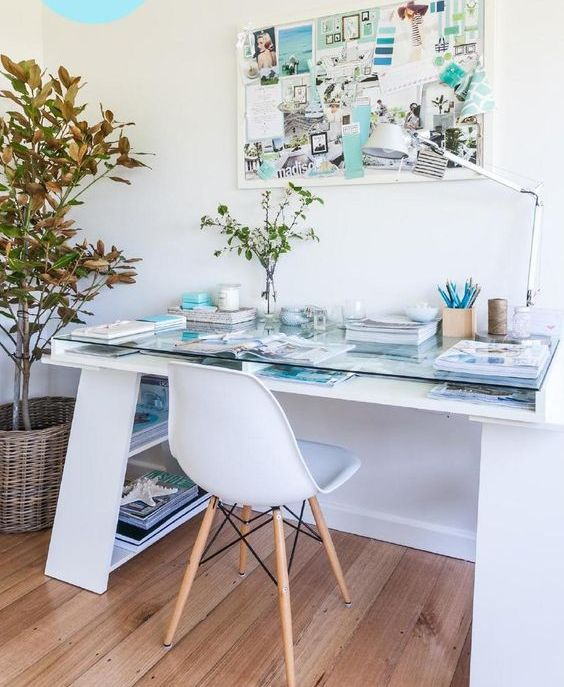 a coastal style home office nook with a desk with a glass top, a white chair, a memo board and some greenery here