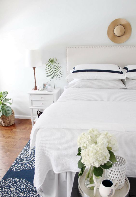 a coastal summer bedroom done in neutrals, with creamy furniture, a printed rug, neutral blooms and greenery and a table lamp