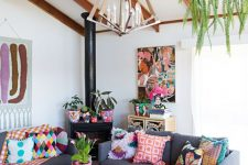 a colorful boho living room with grey sofas, colorful textiles, bold ottomans, a pendant greenery piece and artworks