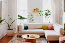 a colorful summer living room with a white sectional, a boho rug and a pouf, a round coffee table, potted plants