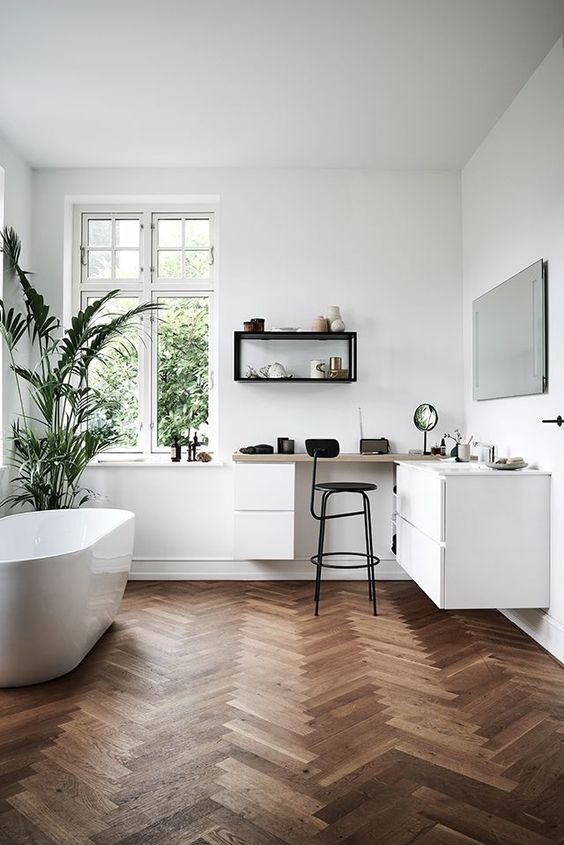 a contemporary bathroom with white walls and dark stained parquet flooring, a white vanity and a white oval tub