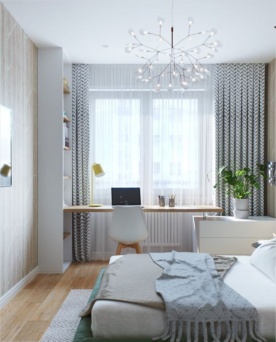 a contemporary bedroom with wallpaper, a working space by the window, with a built-in desk and a large bed plus a quirky chandelier