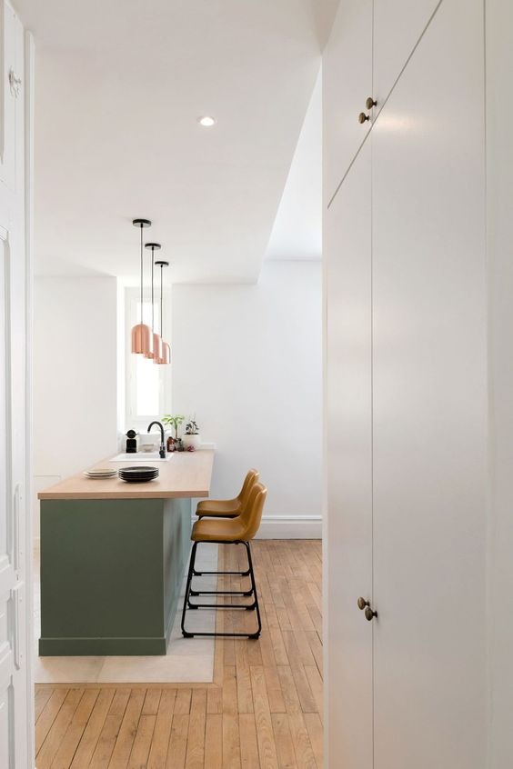 a contemporary kitchen with a green kitchen island with butcherblock countertops, tall leather stools and chic pendant lamps