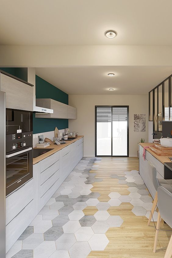 a contemporary kitchen with a transitional hexagon and laminate floor, sleek white cabinets and butcherblock countertops plus an accent wall