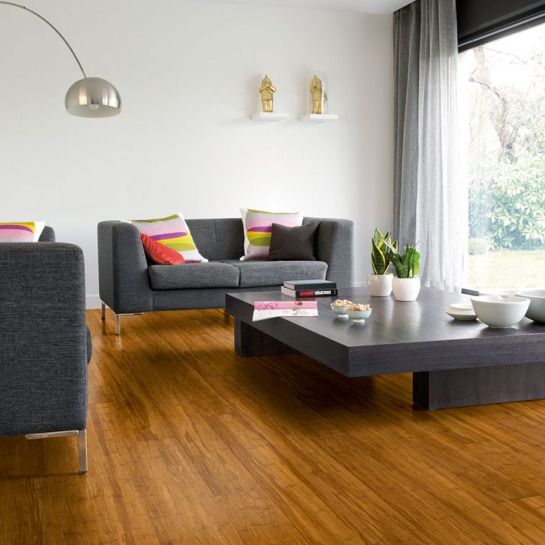 a contemporary living room with white walls and bamboo floors, a glazed wall, elegant grey sofas and a low wooden table