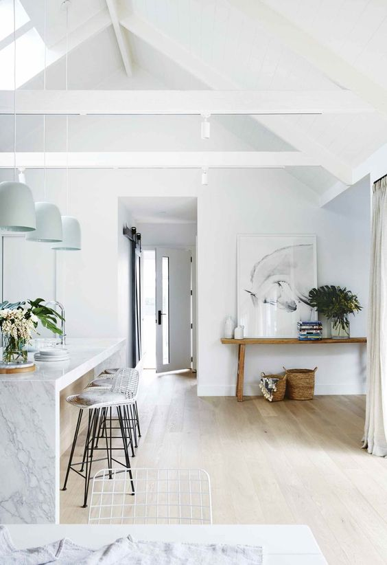 a contemporary space with white walls, a kitchen island with a waterfall countertop, rattan stools and a wooden bench plus greenery
