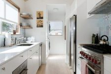 a contemporary white attic kitchen with a blue tile backsplash, white countertops and modern appliances is chic