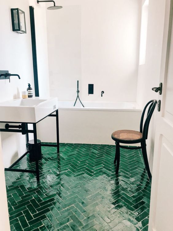 a cool bathroom with neutral walls and an emerald herringbone tile floor, white appliances and black touches for a modern feel