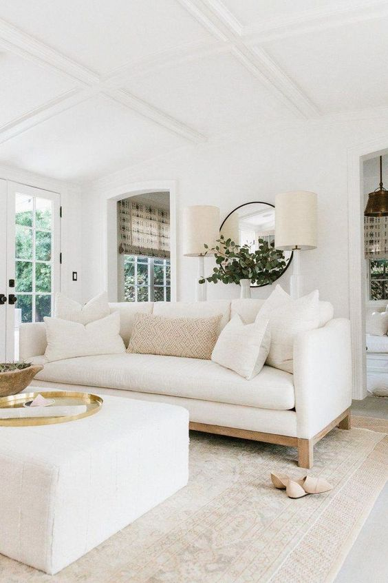a cool living room with a white sofa and a matching ottoman, with a round mirror, two lamps and some chic accessories