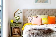 a cool summer bedroom with a grey upholstered bed, colorful printed bedding, a vintage nightstand and a cool lamp