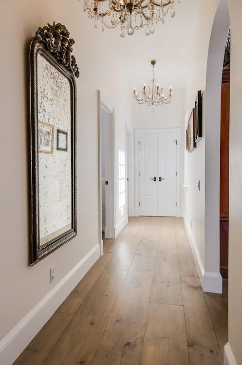 a corridor with white walls and a bamboo floor, a gallery wall and a mirror in a vintage frame plus a crystal chandelier