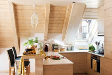 a cozy attic kitchen clad with wood, with light stained cabinetry, pendant lamps, black stools and skylights