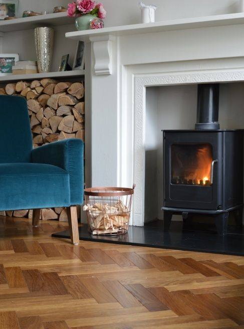 a cozy fireplace nook with lovely parquet floors, a hearth, a navy chair, some firewood stored and a basket