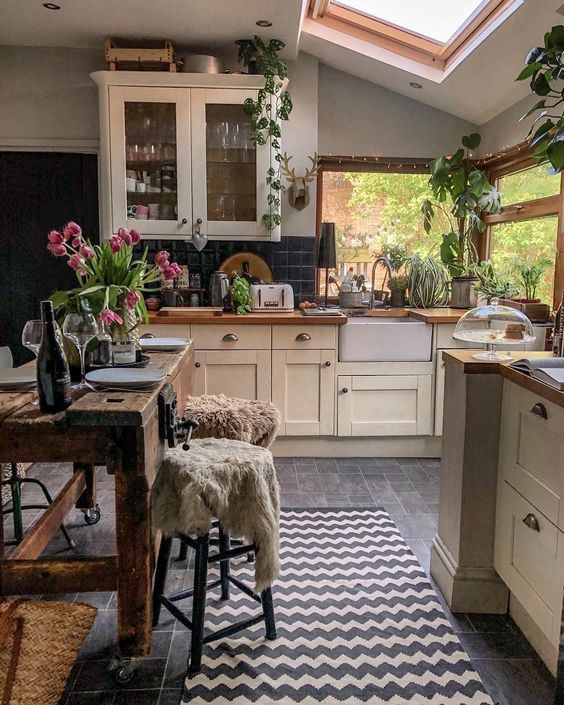 a cozy small kitchen with large windows and a skylight, vintage ivory cabinetry, black square tiles, a rough wooden table and lots of plants