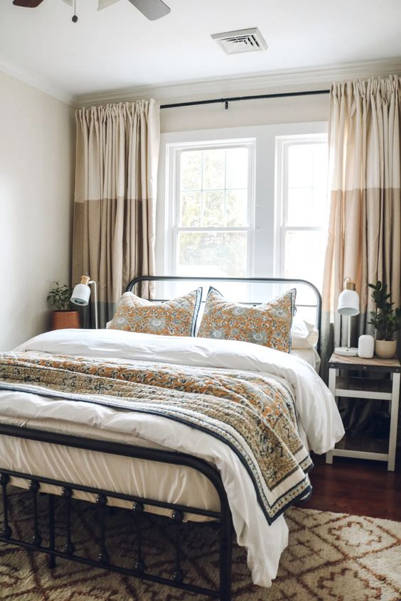 a cozy summer bedroom with a metal bed and mismatching nightstands, neutral printed textiles and potted greenery