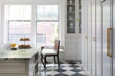 a creamy kitchen and an ivory kitchen island is spruced up with black and white tiles on the floor is a very stylish and cool idea