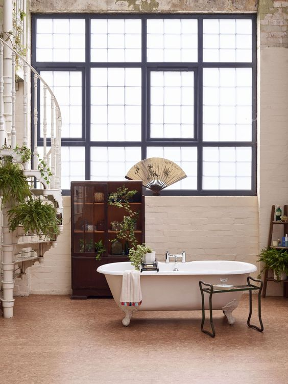 a creative bathroom with white brick walls and a cork wall, a vintage tub, a stand and a dark stained storage unit and potted plants