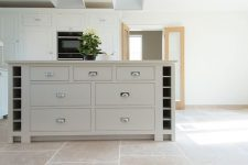 a creative ivory farmhouse kitchen with a tile floor, chic cabinetry with stainless steel knobs and a cool lamp