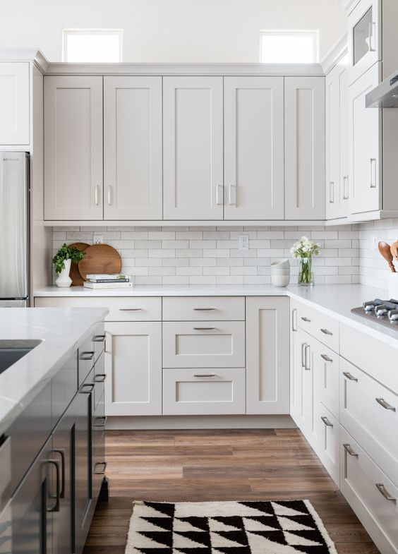 a dove grey farmhouse kitchen with a rich-stained laminate floor, a marble subway tile backsplash and white countertops