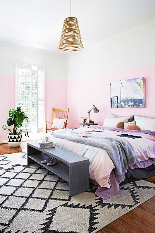 a dreamy summer bedroom with color block pink walls, a comfy bed and a grey bench, a pendant lamp and a potted plant
