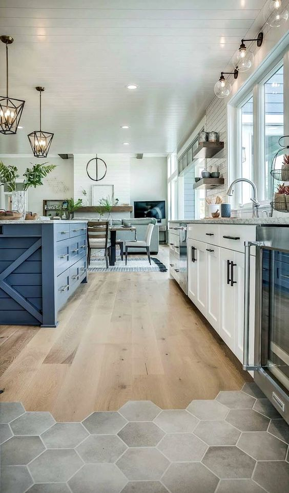 a famrhouse kitchen with white and bold blue cabinetry, a transitional floor from laminate to hexagon tiles and rustic pendant lamps