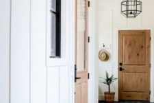 a farmhouse entryway with white paneled walls and a navy chevrong tile floor, wooden doors and pendant lamps