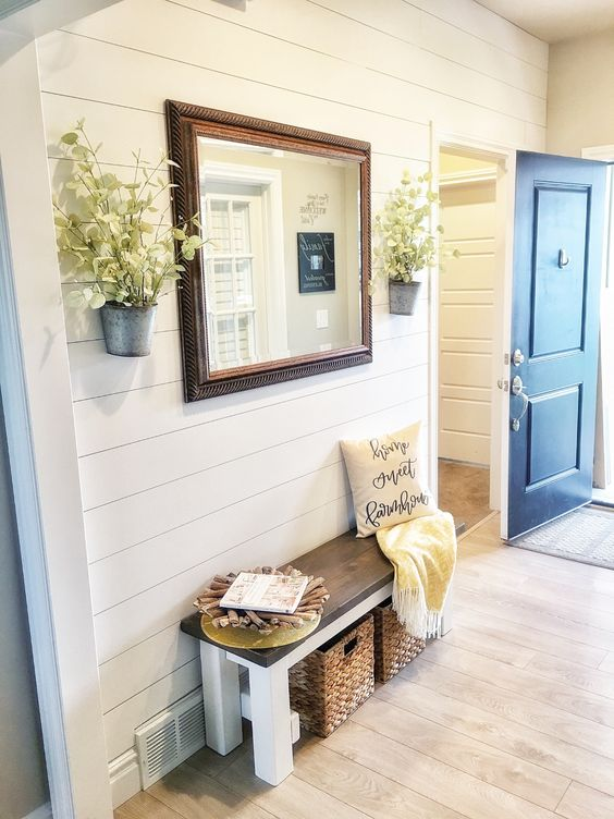 a farmhouse entryway with white planked walls, vinyl floors that imitate wood, a bench, an oversized mirror and potted blooms