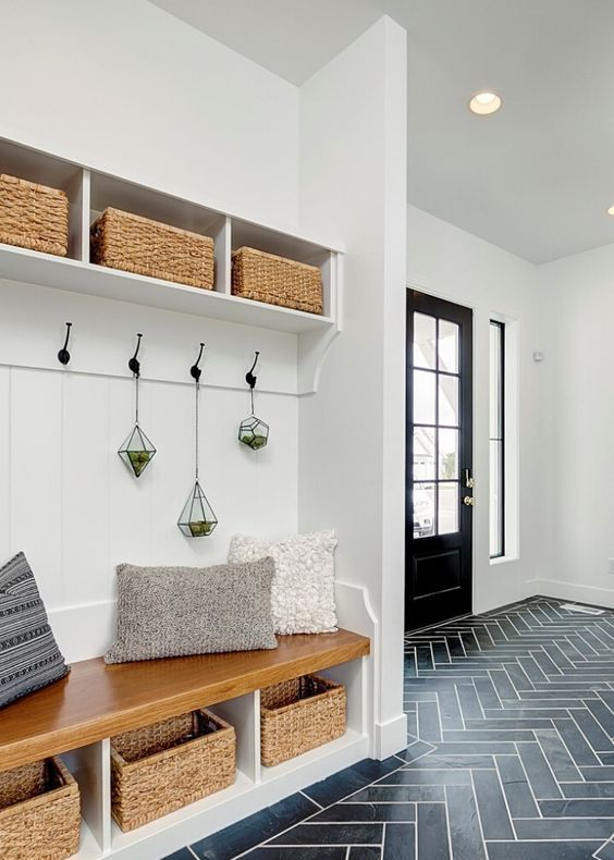 a farmhouse entryway with white walls, a navy tile floor and a lovely built-in storage unit with baskets is a very cool idea