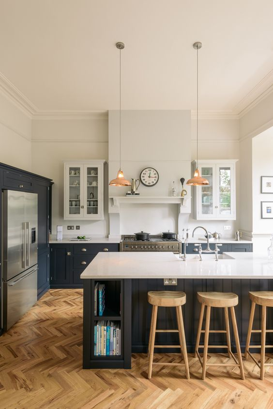 a farmhouse kitchen with light stained parquet flooring, black cabinets with white countertops and chic copper pendant lamps
