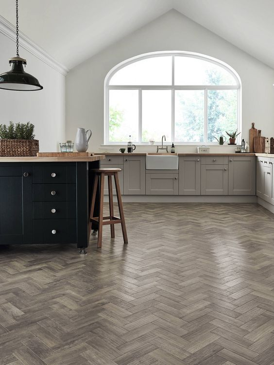 a farmhouse kitchen with white walls, a vinyl floor, grey shaker style cabinets and a black kitchen island, butcherblock countertops and a black lamp