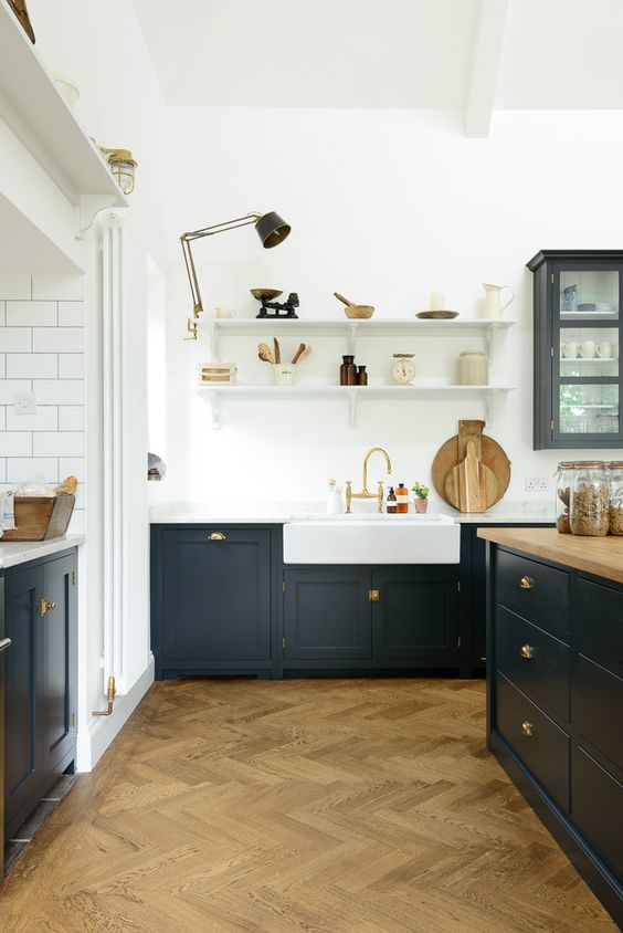 a farmhouse kitchen with white walls and a parquet floor, dark grey cabinets, butcherblock countertops and brass touches