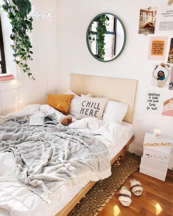a fresh bedroom with a wooden bed, a gallery wall with photos and memos, a jute rug, potted greenery and a round mirror in a green frame