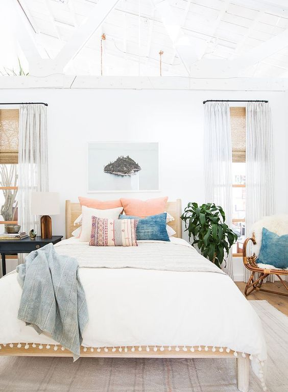 a fresh summer bedroom done in neutrals, with a wooden bed, a rattan chair, printed pillows, a lovely artwork and striped curtains